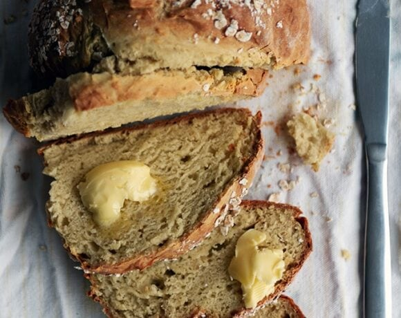 A round no yeast bread on a white kitchen towel, half sliced, some slices topped with butter and a knife on the side.