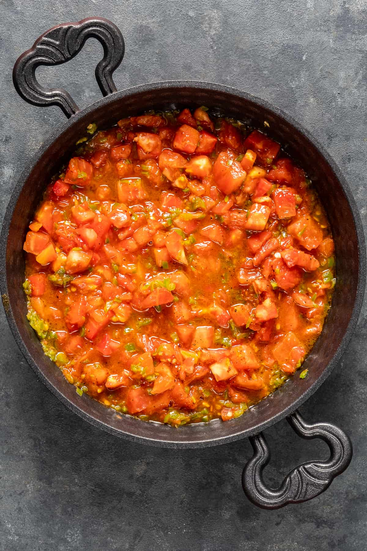 Diced tomatoes and green peppers cooking in a pan