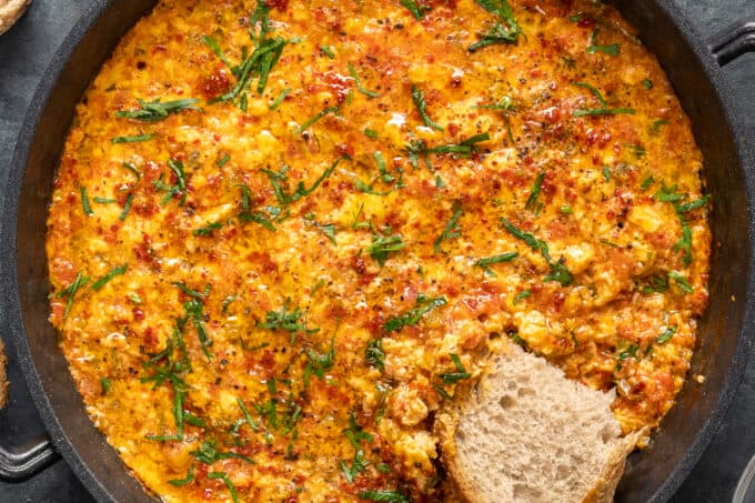 A piece of bread dipped into menemen in a pan.