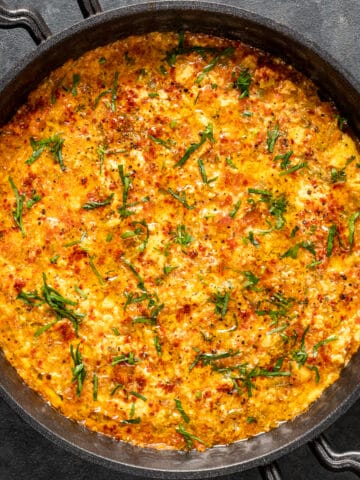 Menemen garnished with chopped parsley in a traditional pan on a dark background.