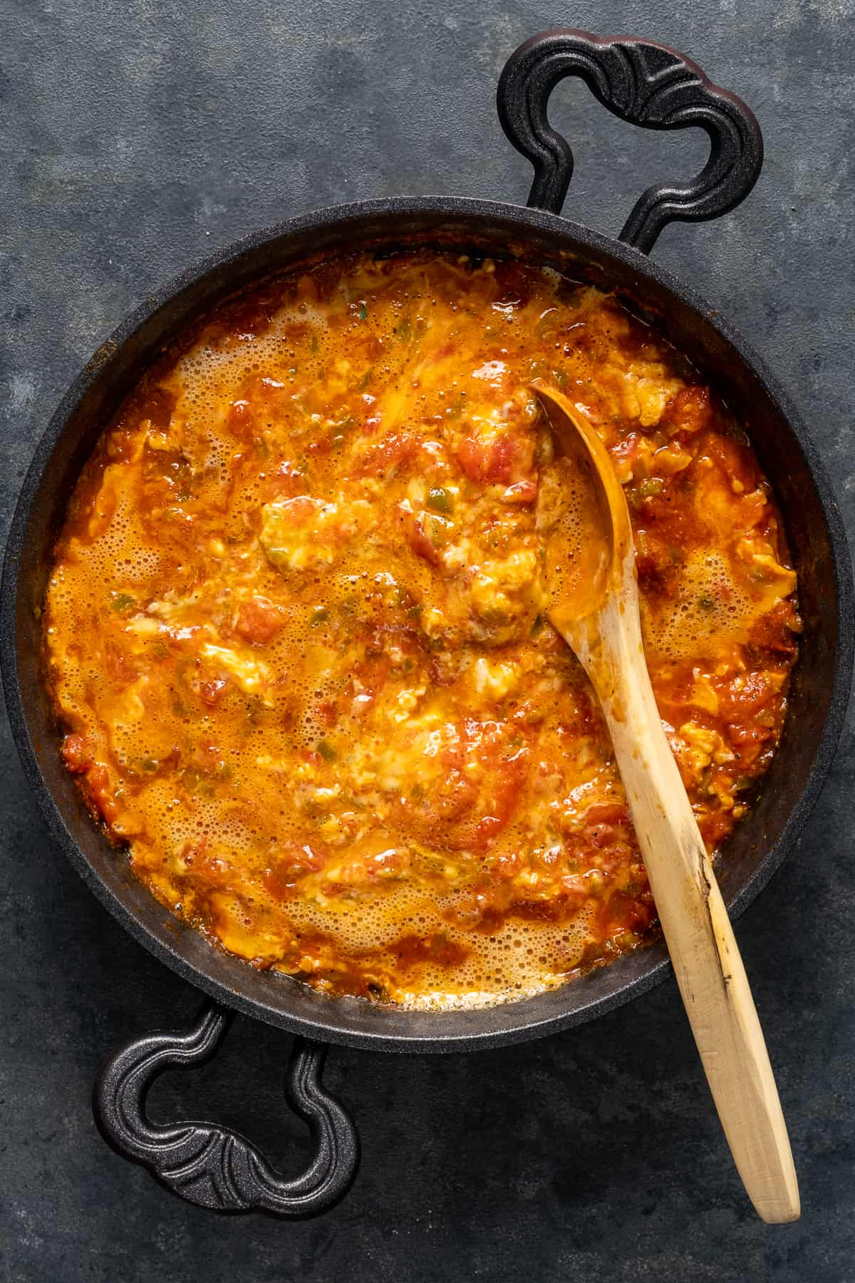 Beaten eggs added into cooking tomatoes and green peppers.
