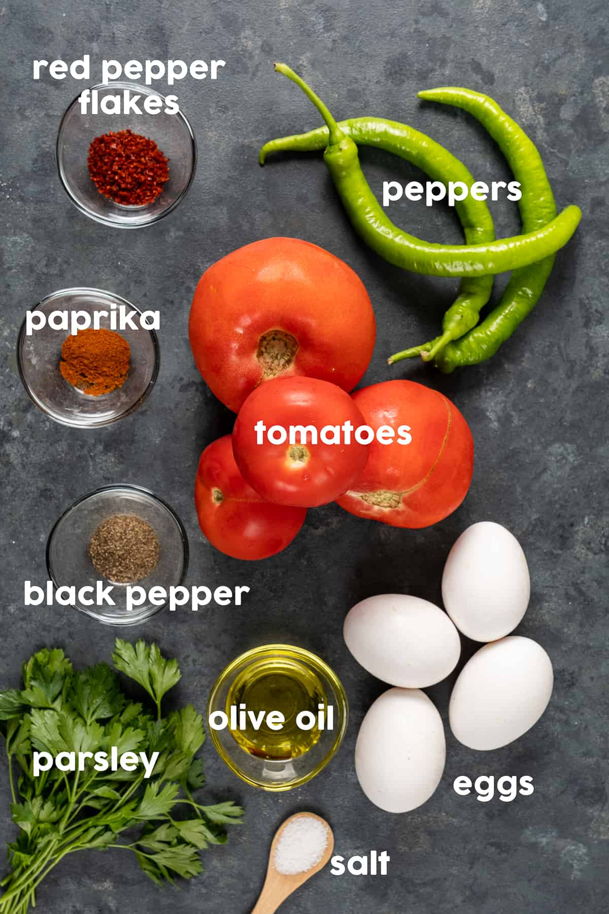 Tomatoes, Turkish green peppers, eggs with their shells, spices, parsley and olive oil on a dark background.
