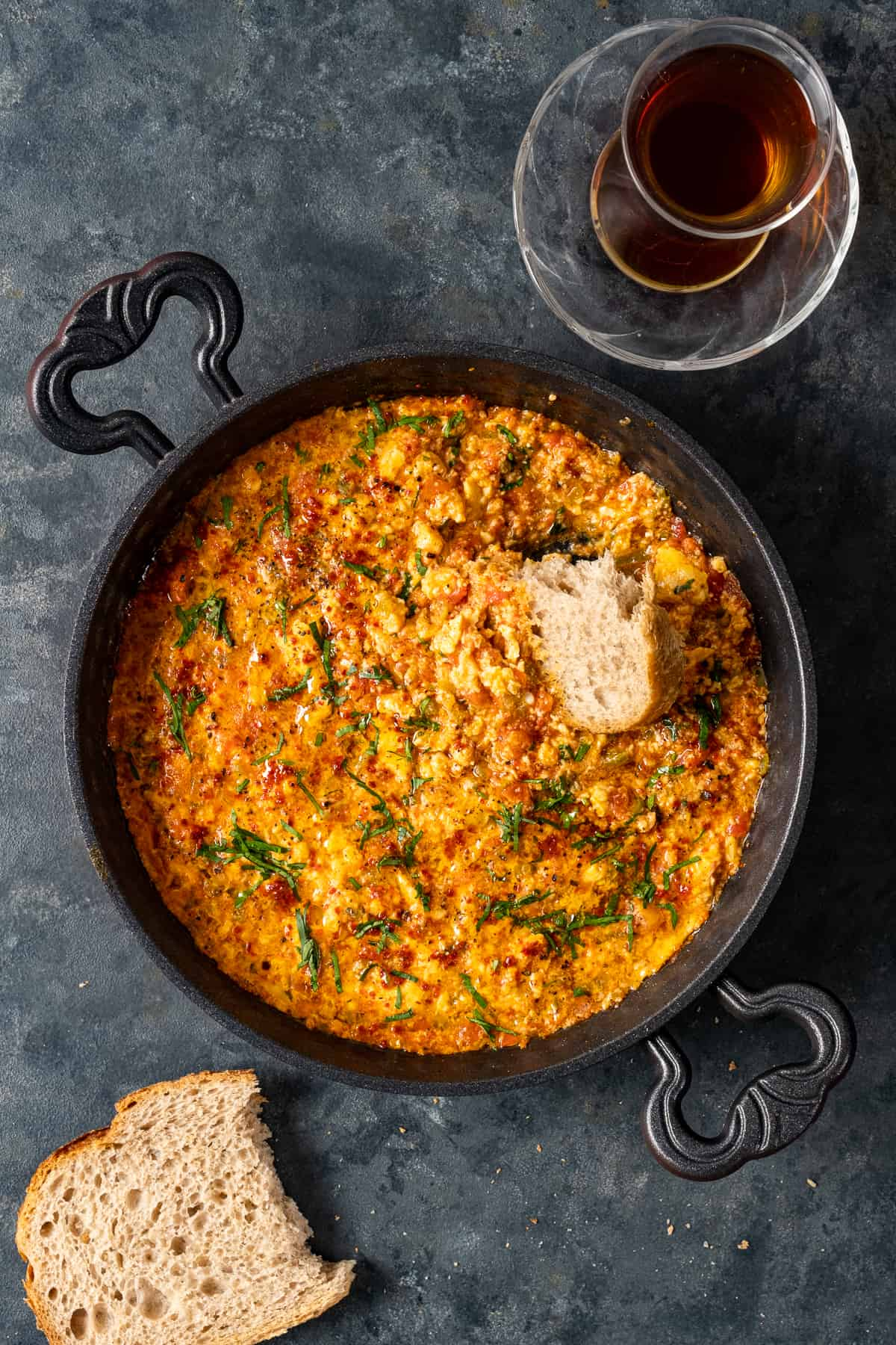 Scrambled eggs with tomatoes and peppers aka menemen in a pan accompanied by a glass of Turkish tea and bread slices.
