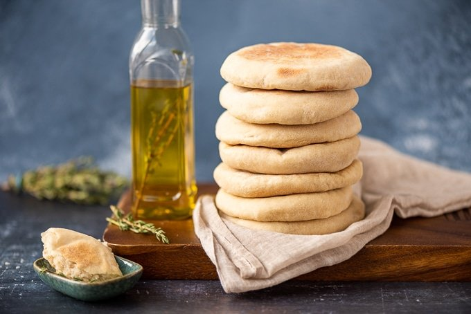 A stack of Turkish flatbread called bazlama on a wooden board, a bottle of olive oil, fresh thyme and a small bowl accompany.