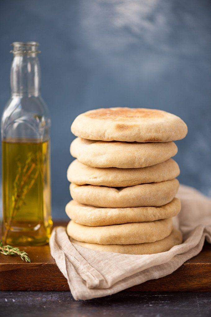 A stack of Turkish flatbread called bazlama on a wooden board, a bottle of olive oil and fresh thyme accompany.