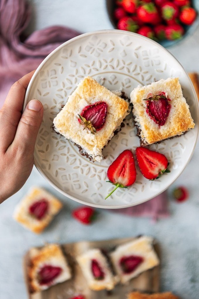 A hand holding a white plate with two slices of coconut ice squares with chocolate bottom and strawberry topping photographed on a light background. Fresh strawberries and a wooden serving board accompany.