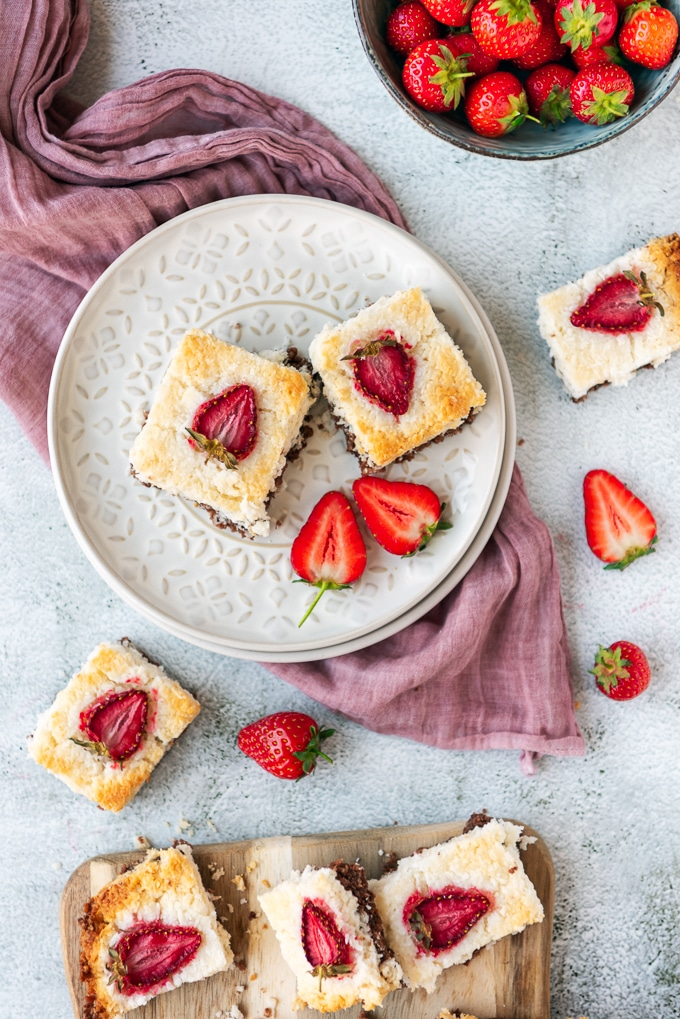 Two slices of coconut ice squares with chocolate bottom and strawberry topping on a white ceramic plate photographed on a light background. Fresh strawberries and a wooden serving board accompany.