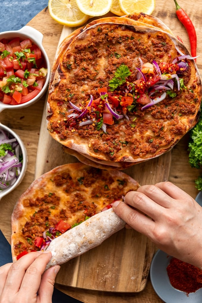 Hands rolling up a lahmacun on a wooden board with some more lahmacun portions and condiments like red onion salad, tomato salad, lemon slices, chili pepper and parsley.