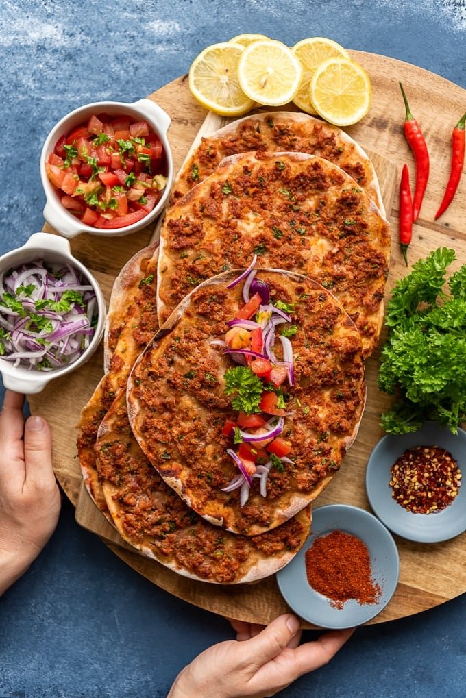 Turkish homemade flatbread lahmajun on a wooden board accompanied by onion salad, tomato sald, parsley, lemon slices and chili peppers.