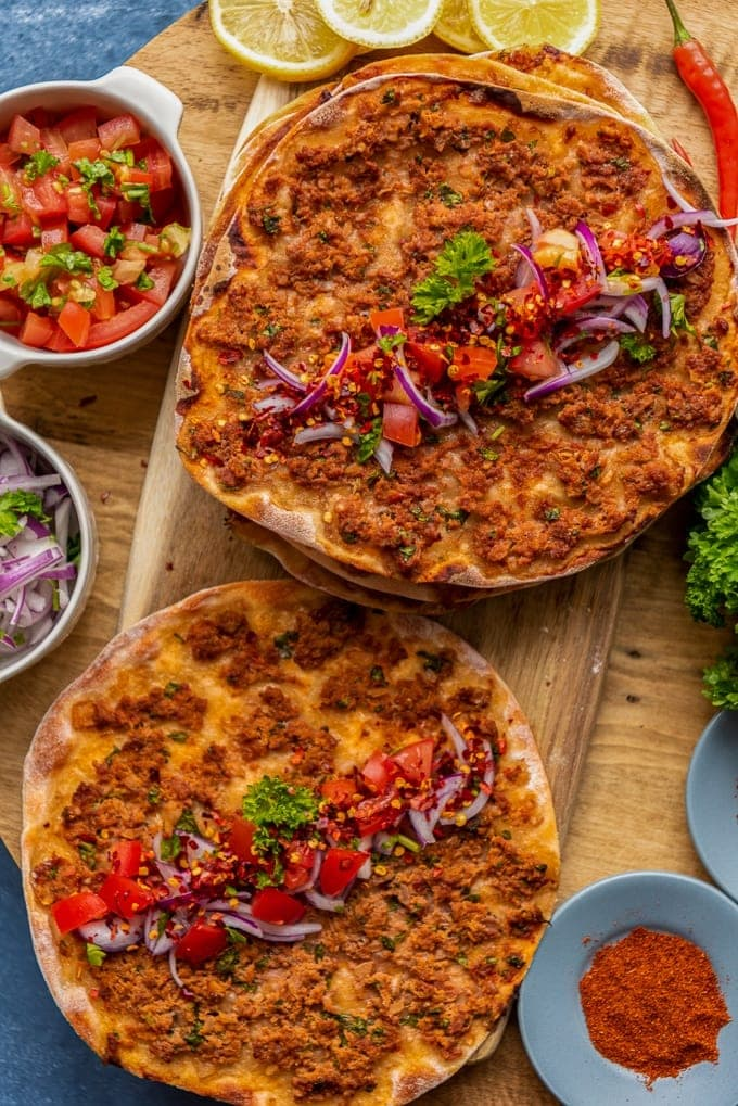 Turkish lahmacun stacked on a wooden board, topped with onions, tomatoes and parsley.