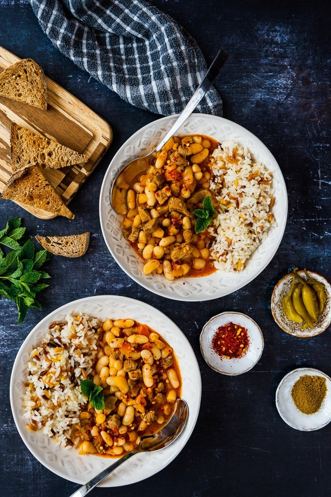 Turkish white bean stew with lamb called kuru fasulye served with orzo rice pilaf on the side in two white bowls. Bread slices, fresh mint, pickles and spices accompany.