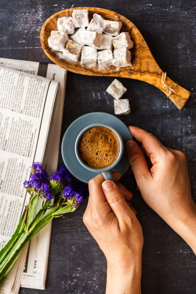 Woman holding Turkish coffee in a grey coffee cup accompanied by purple flowers, newspaper and Turkish delights on a dark background.