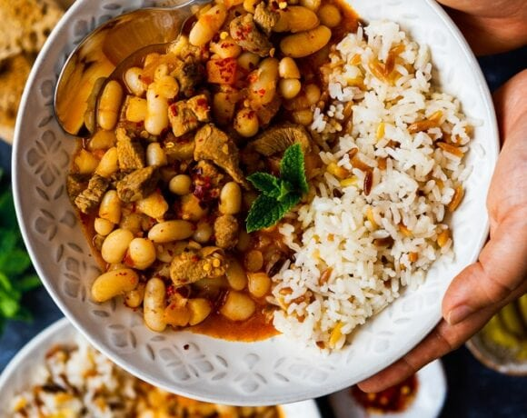Hands holding a bowl with Turkish white bean stew with lamb and orzo sice pilaf on the side.