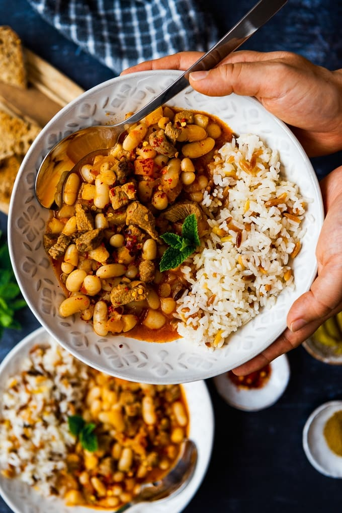 Hands holding a bowl with Turkish white bean stew with lamb and orzo rice pilaf on the side.