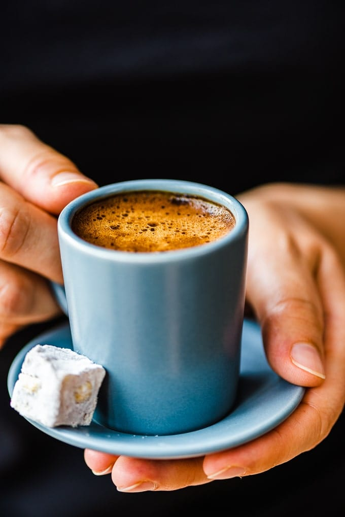 Woman with a black sweater holding Turkish coffee in a grey coffee cup, a pistachio Turkish delight on the side.