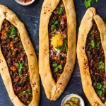 Turkish pide stuffed with beef and an egg accompanied by crushed chillies, pickles and parsley on a dark background.