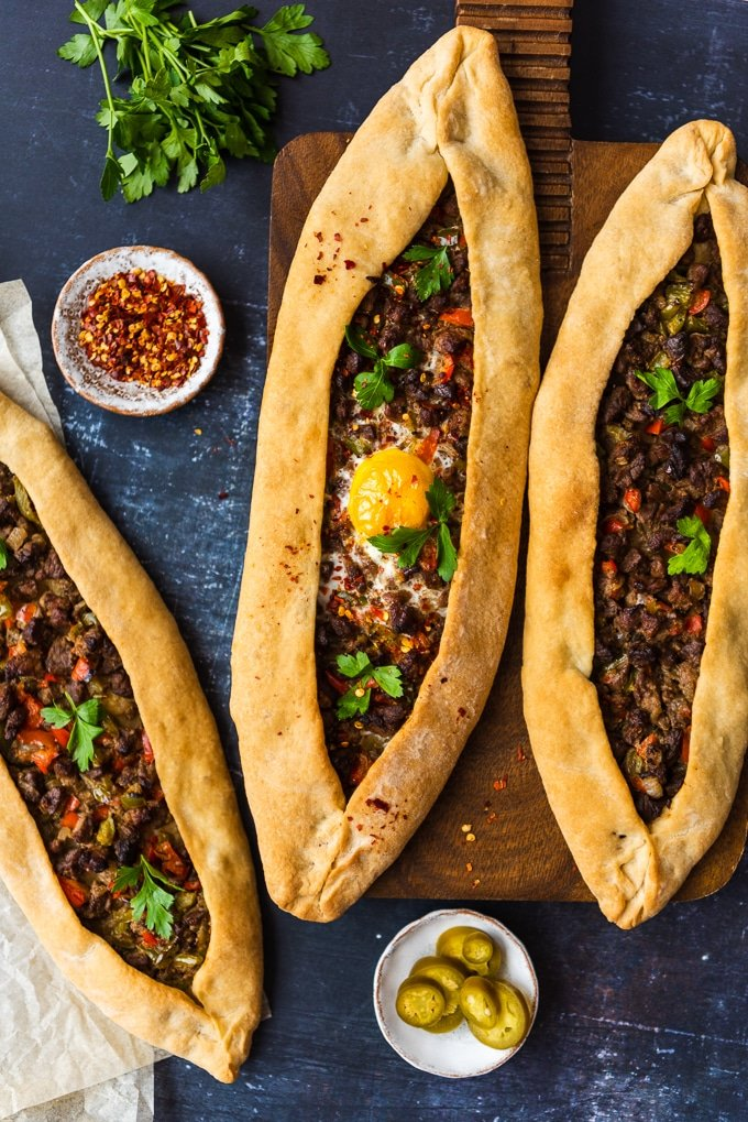 Turkish flatbread pizza pide stuffed with beef and an egg on a wooden board and on the ground accompanied by crushed chillies, pickles and parsley photographed on a dark background.