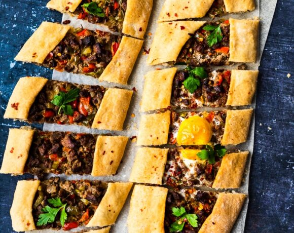 Turkish pide stuffed with beef sliced on a piece of baking paper on a dark background.