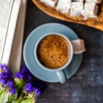 Turkish coffee served in a grey coffee cup and accompanied by Turkish delights, wild flowers and newspaper on a dark background.