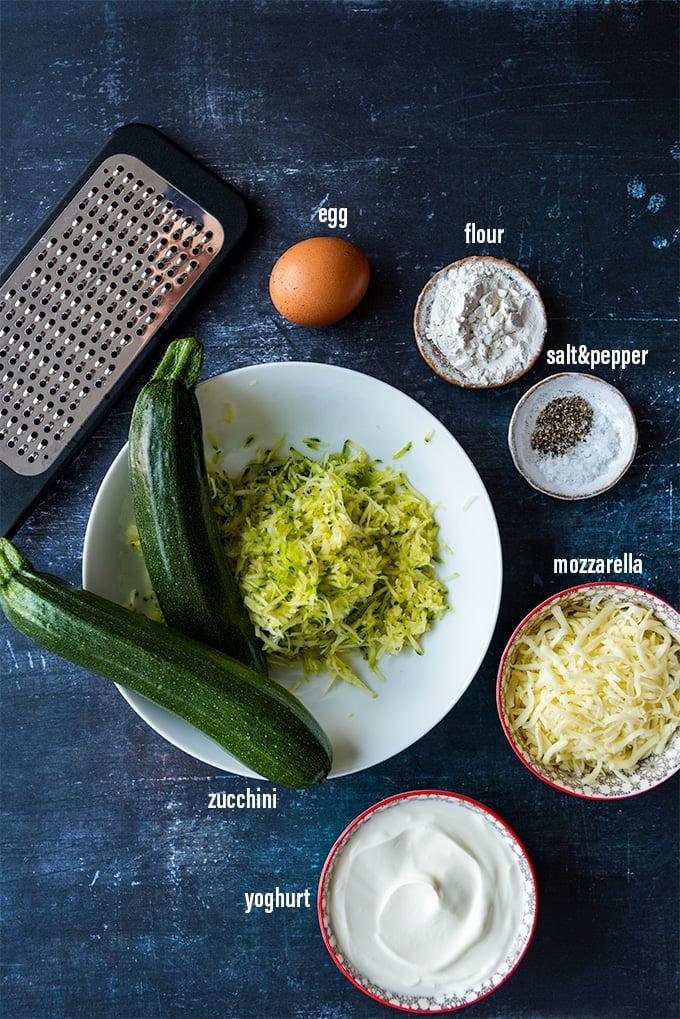Zucchini cheese casserole ingredients on a dark background.