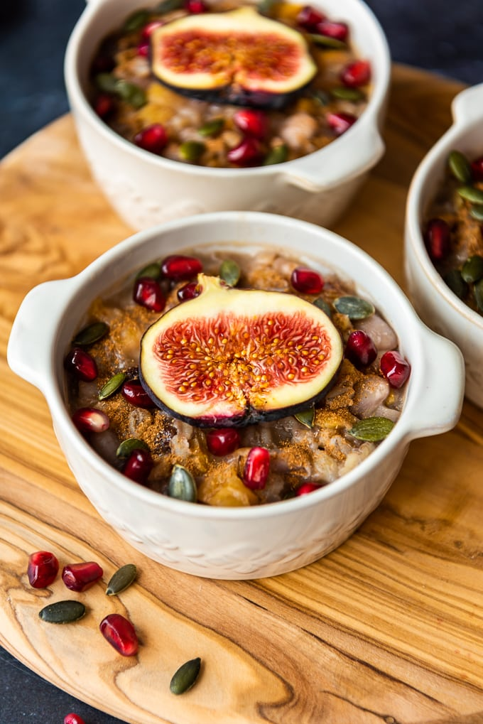 Ashura dessert with grains and fruit in white bowls on a wooden board.