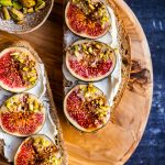 Two bread slices topped with cream cheese and fresh figs dipped coated with tahini and crumbled pistachios on a round wooden board.