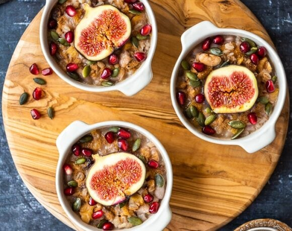 Turkish asure pudding garnished with pomegranate arils, fresh figs and pumpkin seeds in white bowls on a round wooden board.