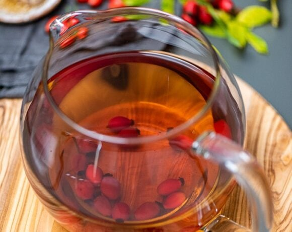 Fresh rose hip tea in a glass teapot on a wooden board, fresh rosehips and honey dipper on the side.