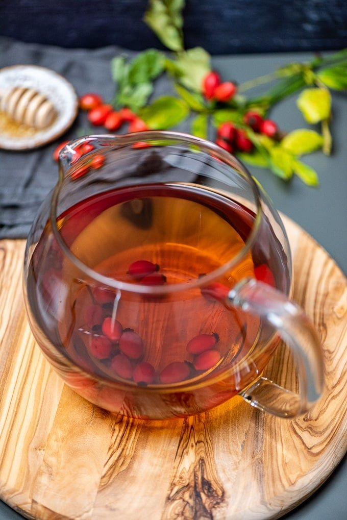 Fresh rose hip tea in a glass teapot on a round wooden board.