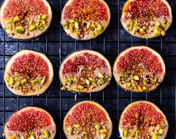 Tahini dipped fresh figs garnished with pistachio and sesame seeds on a dark background.
