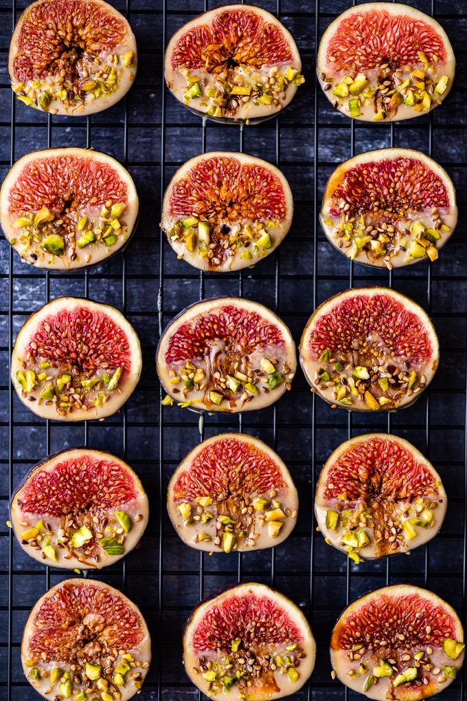 Fresh figs dipped into tahini, sweetened with date molasses, garnished with pistachios and sesame seeds on a background.