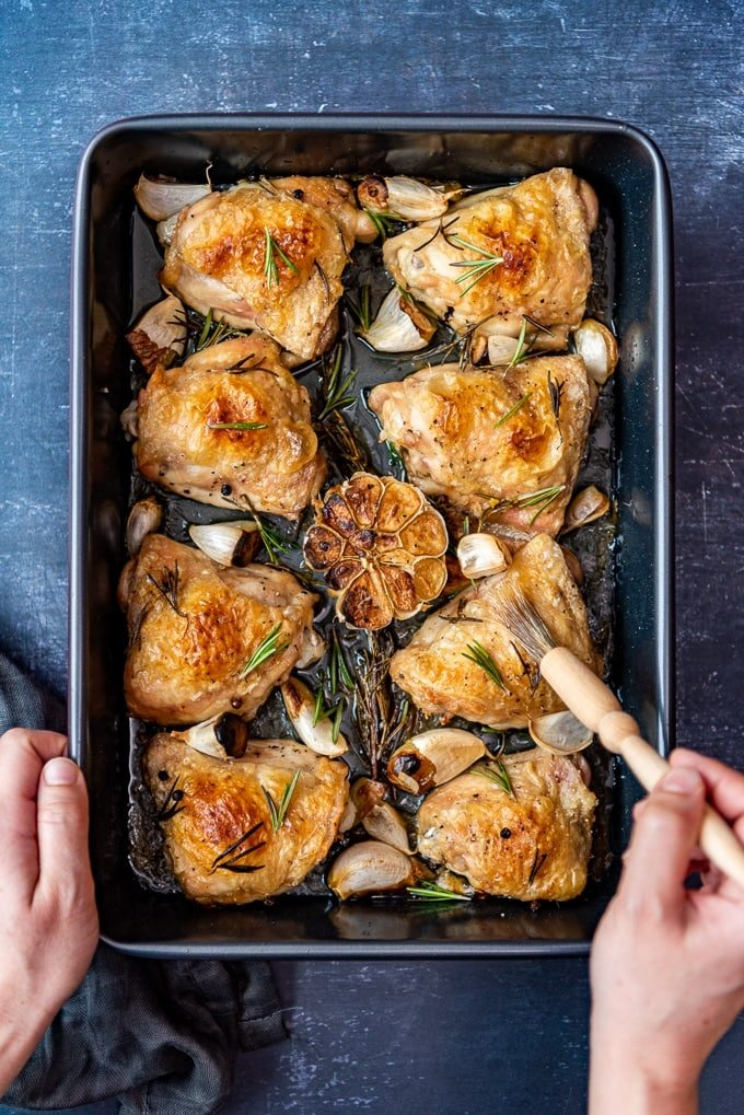 Brushing chicken thighs with the juice in the baking pan