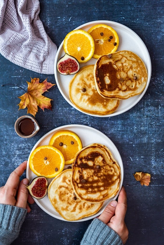 Dairy free pancakes served with oranges, figs and maple syrup on two white plates.