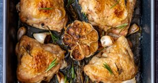 Golden and crispy skin baked chicken pieces with garlic and rosemary in a roasting pan.