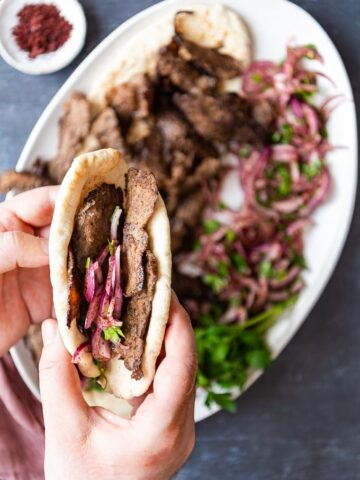 Hands holding doner kebab sandwich with sumac onions.