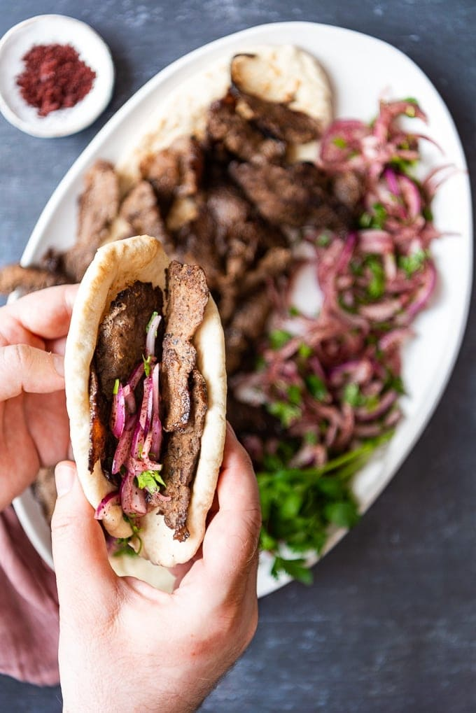 Holding Doner Kebab Sandwich with onions