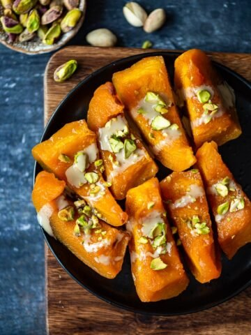 Turkish pumpkin dessert with tahini and pistachios on a black plate.
