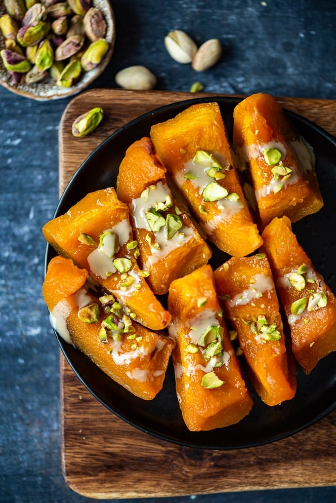 Turkish pumpkin dessert with tahini and pistachios on a black plate