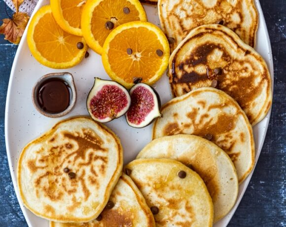 Almond milk pancakes served with orange slices, figs and maple syrup on a white oval plate.