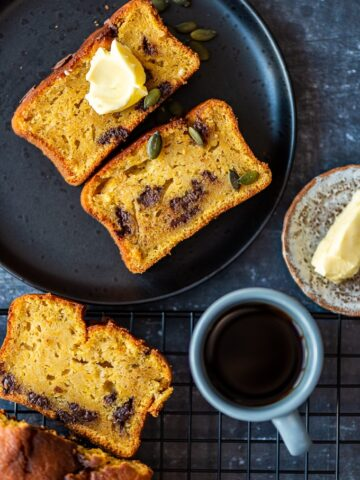 Pumpkin loaf cake slices with chocolate chips served on a black plate, a cup of coffee on a wire rack on the side.