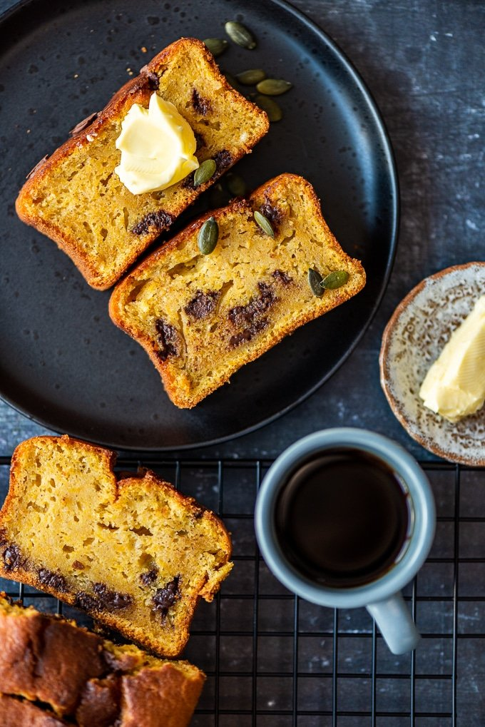 Chocolate chip pumpkin loaf cake slices on a black plate, garnished with pumpkin seeds and on a cooling rack accompanied by coffee and butter.
