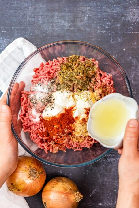 A hand pouring onion juice over ground beef doner meat ingredients in a large glass bowl.