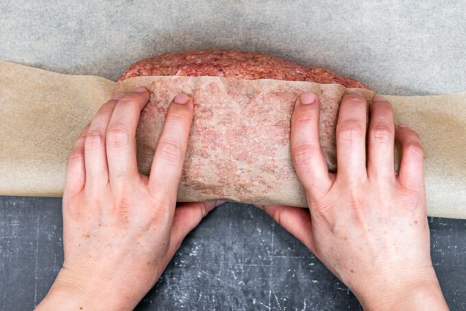 Hands wrapping a log of doner kebab meat with brown baking paper.