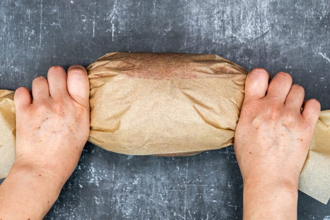 Hands tightening a log of beef doner that is wrapped with brown baking paper from two sides.