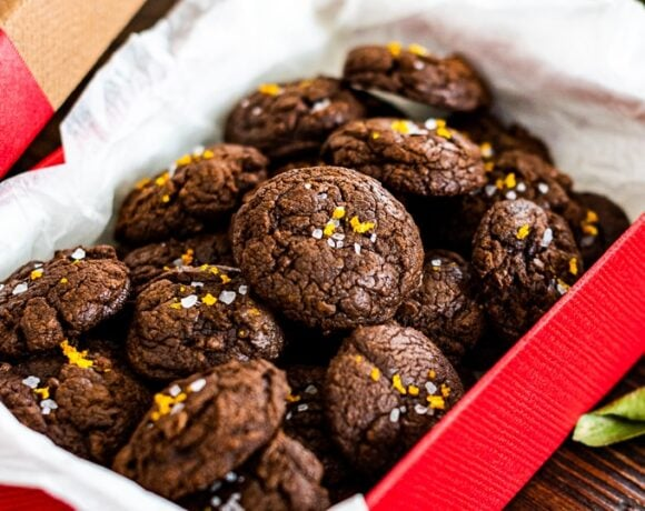 Chocolate brownie cookies with orange zest and sea salt in a red gift box.