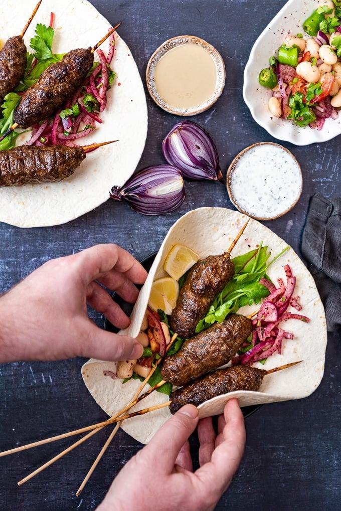Holding kofta skewers on lavash with onions and salad.