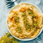 Turkish halva made with flour and syrup served on a white plate with ground pistachio