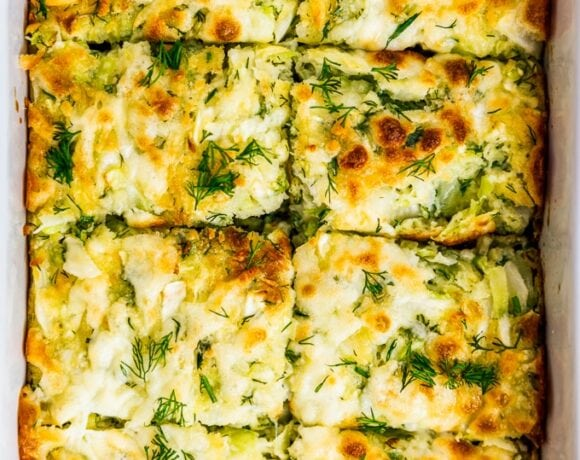 Cheesy cabbage casserole with fresh dill in a baking pan.