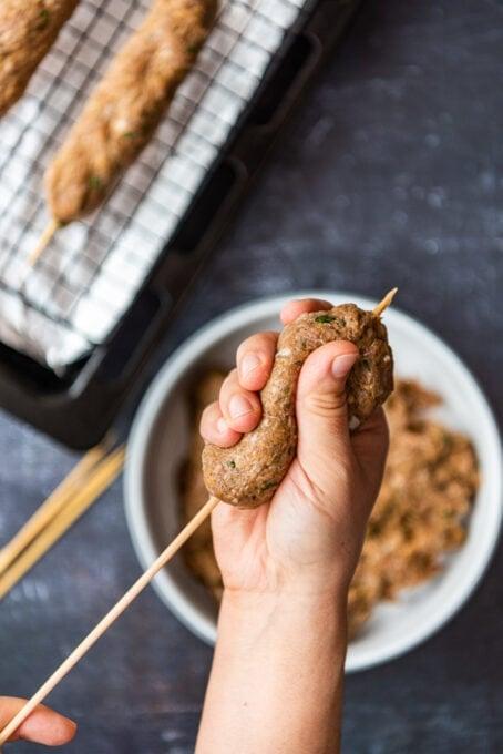 hands shaping kefta kabob on wooden skewers