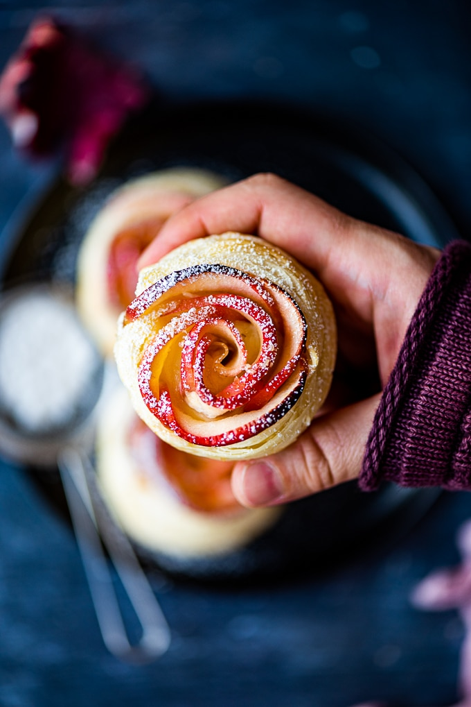 Holding a mini apple rose tart with powdered sugar